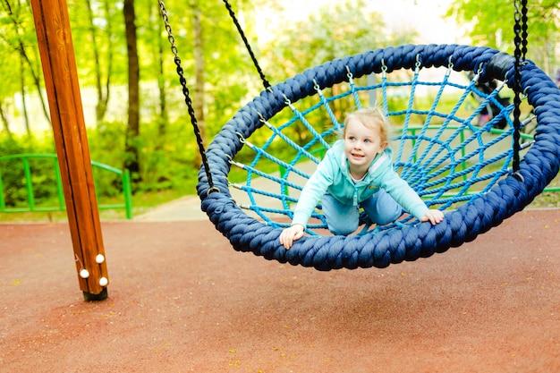 4歳のかわいい白人の幼児の女の子が遊び場のスライドで楽しんで