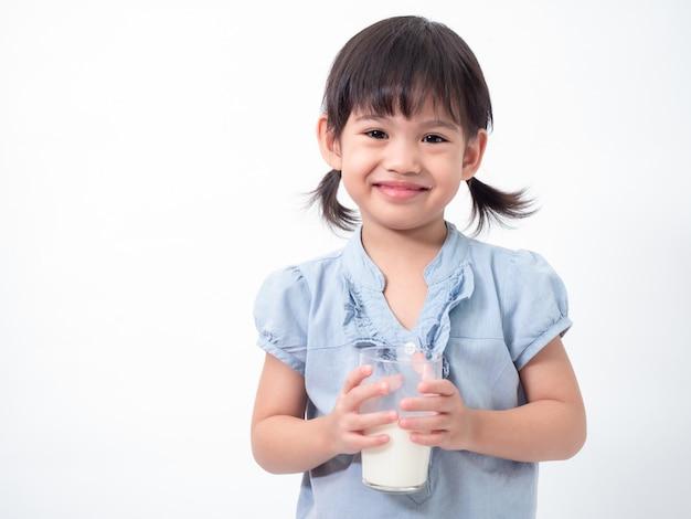 アジアのかわいい女の子4歳保持し、白で眼鏡から牛乳を飲む