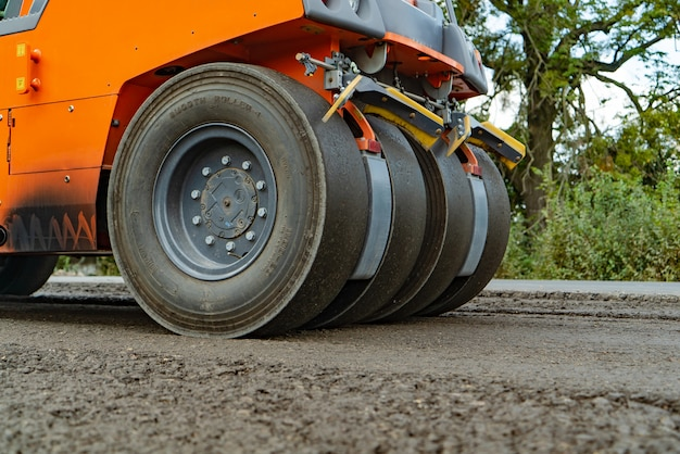 4つの車輪が付いているアスファルトのためのオレンジ色のスチームローラーは、日に道路に立っています。