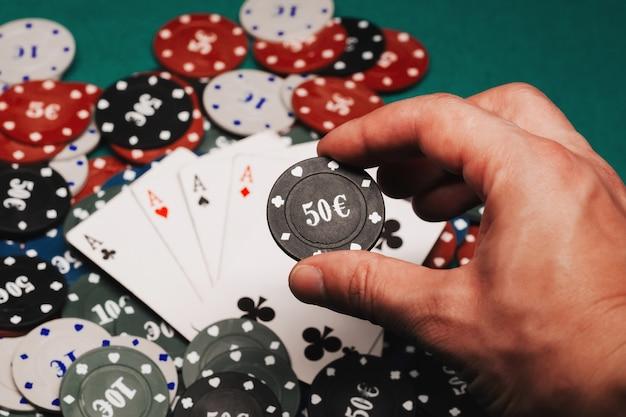カジノの緑のテーブルにあるゲームチップの山にある4種類のエース
