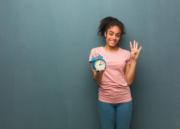番号4を示す若い黒人女性。彼女は目覚まし時計を持っています。