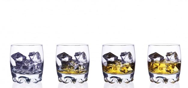 Стекло 4 вискиов с кубиками льда на белом изоляте предпосылки.