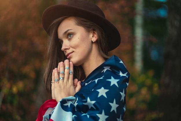 Портрет привлекательной патриотической инди женщины в шляпе с американским флагом носить серебряные кольца с бирюзовым камнем на открытом воздухе. путешествие в америку и празднование праздника 4 июля в сша