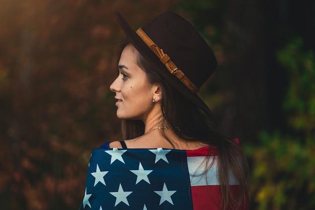 Портрет привлекательной патриотической брюнетки инди-женщины с длинными волосами в коричневой шляпе с американским флагом на открытом воздухе. путешествие в америку и празднование праздника 4 июля в сша