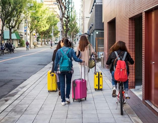 トロリーバッグを持った4人の若いティーンエージャーの友人のグループが、東京、日本で旅行します。
