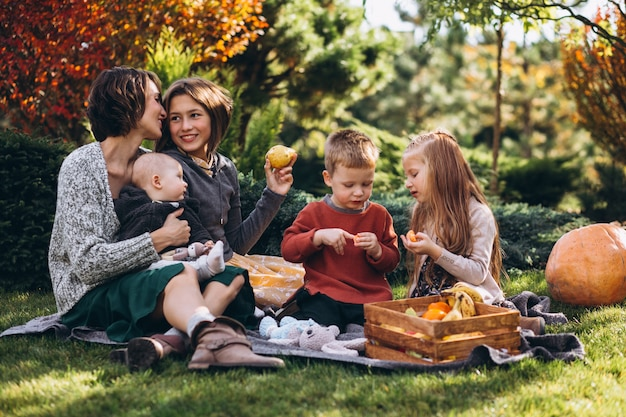 裏庭でピクニックを持つ4人の子供を持つ母