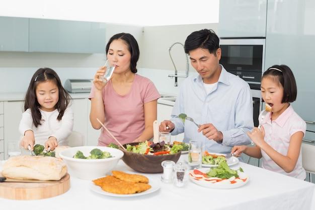 キッチンで健康的な食事を楽しむ4人の若い家族