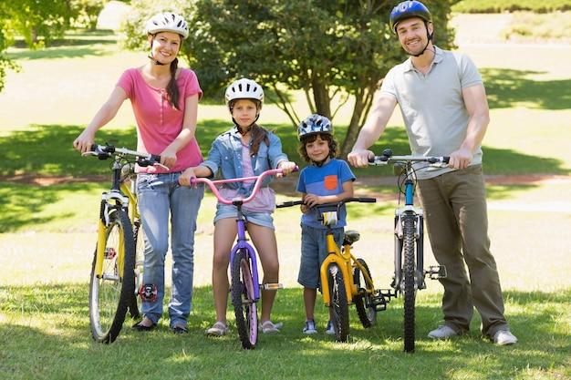 公園に自転車を持っている4人の家族