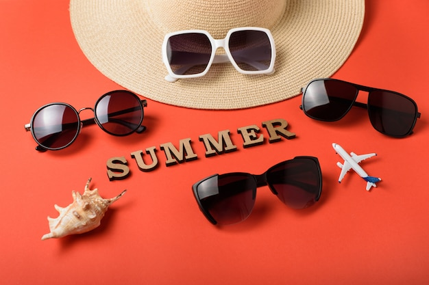 木製の手紙から単語夏。 4つのサングラス、帽子と貝殻の一部。サンゴのライブ背景。旅行のコンセプト