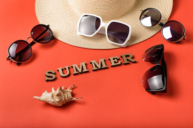 木製の手紙から単語夏。 4つのサングラス、帽子と貝殻の一部。
