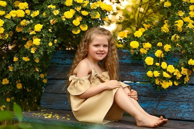 黄色いバラの茂みの下のベンチに座っている4歳の女の子。ベージュのドレスを着て、彼の顔に笑みを浮かべてフレームを見ています。裸足の巻き毛。