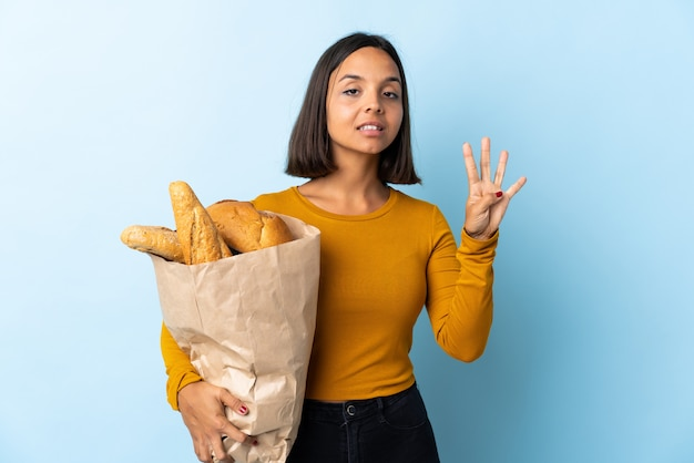 Молодая латинская женщина покупая некоторые хлебы изолированные на голубом счастливом и подсчитывая 4 с пальцами