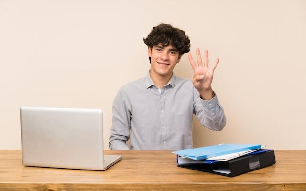 幸せと指で4つを数えるラップトップを持つ若い学生男