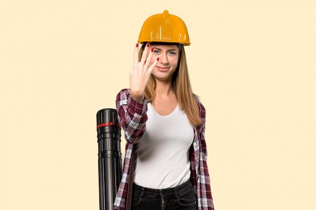建築家の女性の幸せと分離の黄色の壁の上の指で4つを数える