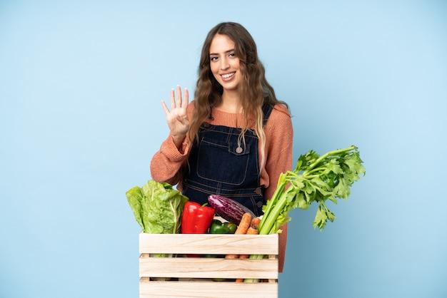 幸せと指で4つを数えるボックスで摘みたての野菜を持つ農家