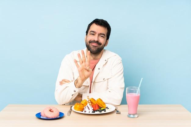 朝食ワッフルとミルクセーキ幸せと指で4つを数えるテーブルで男
