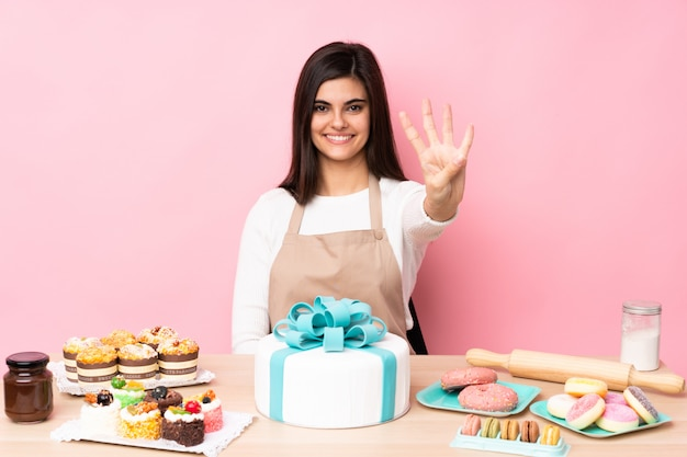 ピンクの壁の上のテーブルに大きなケーキとパティシエ幸せと指で4つを数える