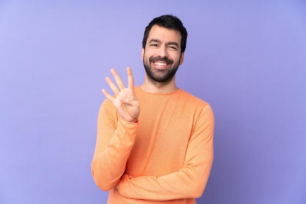 幸せと指で4つを数える紫色の壁の上の白人のハンサムな男