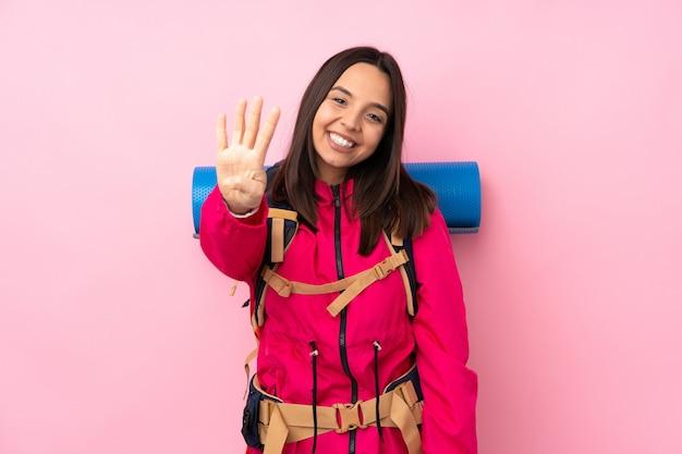 ピンクの幸せと指で4つを数える大きなバックパックを持つ登山少女