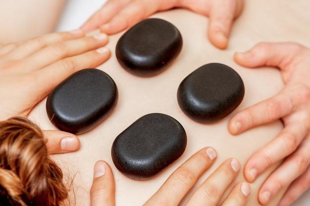 男性の4つの手が女性の背中に石を置く