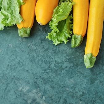 キッチンテーブルの上の4つの黄色いズッキーニとレタス。生のズッキーニ
