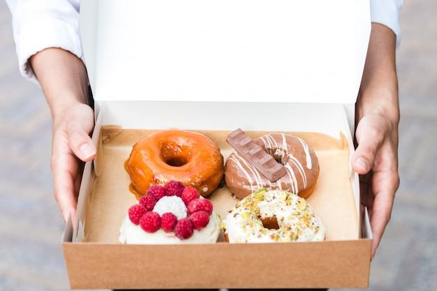 Закройте вверх по рукам держа 4 части совершенно различных красочных и очень вкусных смотря пончиков в экологической коробке коробки. аппетитный десерт быстрого питания