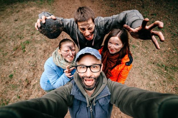 4人のクレイジー面白い人の自撮り。奇妙な怖い会社が屋外で混乱しています。気味悪い不気味な仲間が浮気します。異常な汚れた顔の感情。広角歪み。邪悪な家族。表現力豊かな男性、女性