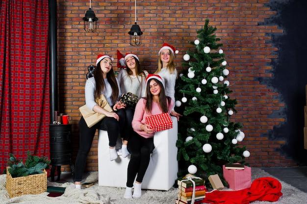 4人のかわいい友人の女の子が暖かいセーター、黒いズボン、クリスマスの飾りが付いている木に対してサンタの帽子を着ています。