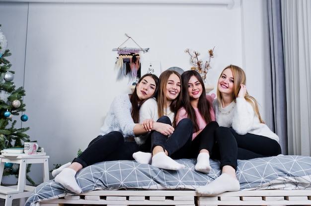 4人のかわいい友人の女の子は、スタジオの装飾が施された部屋のベッドで暖かいセーターと黒いズボンを着ています。