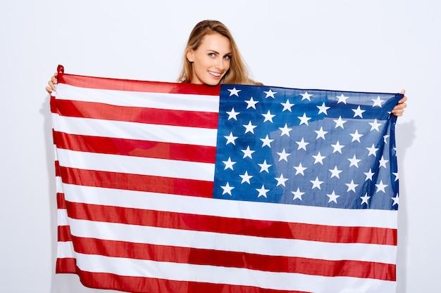 Я люблю сша. женщина держит американский флаг на белом фоне и улыбкой. концепция миграции, национальных праздников и национальных праздников и дня независимости америки 4 июля