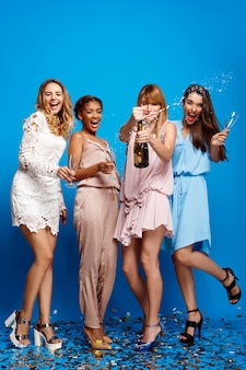 水色の壁の上のパーティーで休んで4人の美しい女の子
