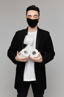 Красивый молодой человек в черной защитной маске держа 4 изолированного рулона туалетной бумаги ,. молодые люди в защитной маске позирует с туалетной бумагой