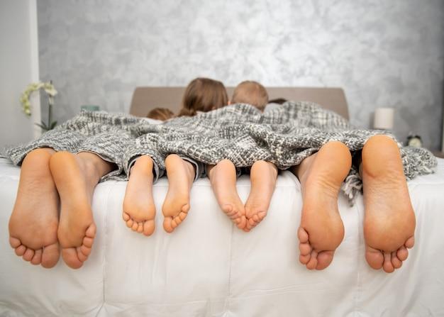 家にいる、ベッドの上に4組の足、親と子供