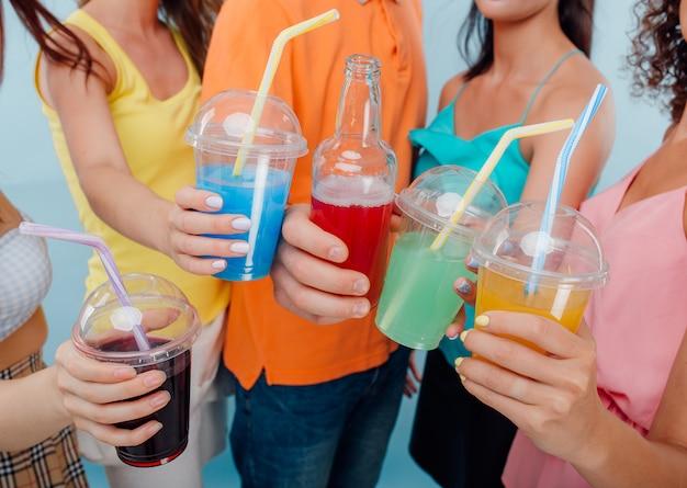 4つのプラスチックカップと異なるジュース色のボトルのクローズアップ