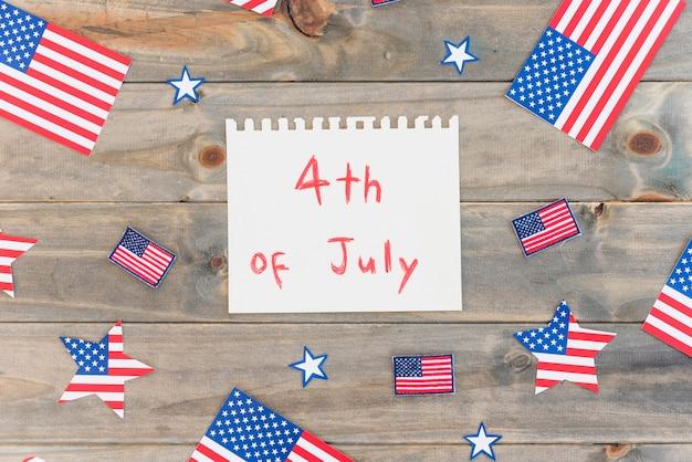 Бумага с текстом 4 июля и многими флагами сша