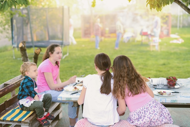 自然の中でテーブルのそばに座って食べている4人の子供