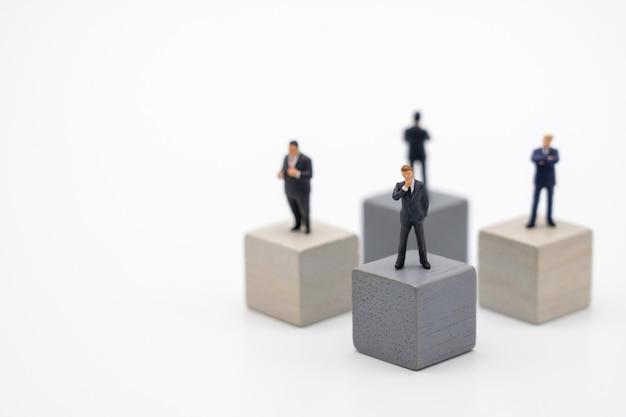 木製キューブ投資分析の上に立ってミニチュア4人のビジネスマン