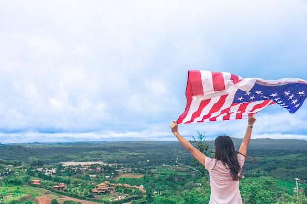 Молодые женщины поднимают национальный американский флаг против голубого неба. день независимости, 4 июля
