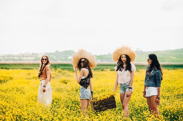 黄色の花の分野で4つの美しいヒッピーの女の子