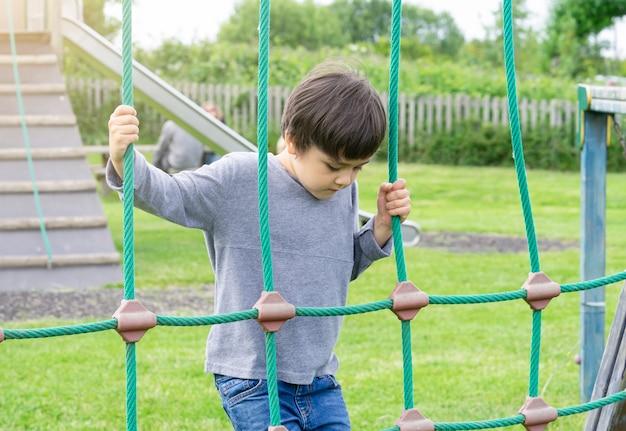 屋外で遊ぶアクティブな少年、遊び場でロープを登る4歳の子供、夏の日のクライミングアドベンチャーパークでの活動を楽しんで幸せな子供