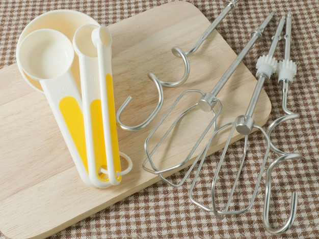 様々なサイズの4つのプラスチック測定スプーンは、木製の切削板に金属泡立て器
