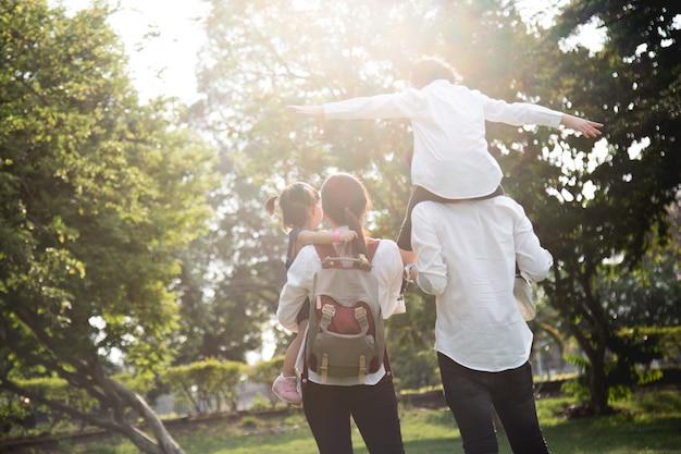 芝生の上を歩く4人家族、娘を与える父は公園で首に乗る。