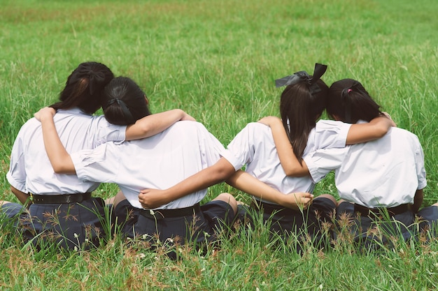 Девушка 4 студентов обнимает в поле, концепции лучших другов.