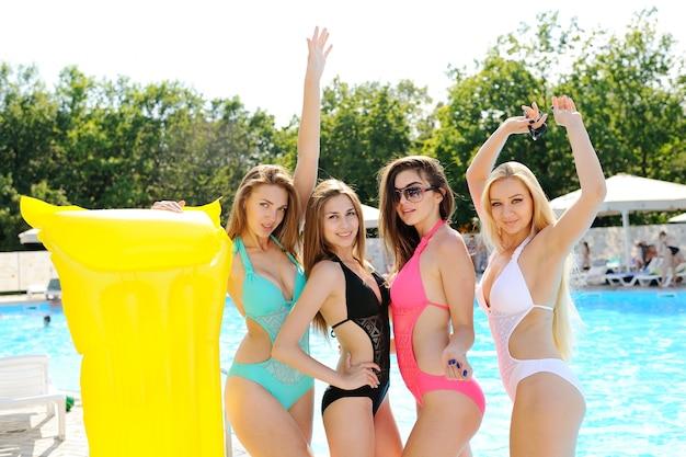 黄色の膨脹可能なマットレスとカラフルな水着の4つの魅力的なガールフレンド