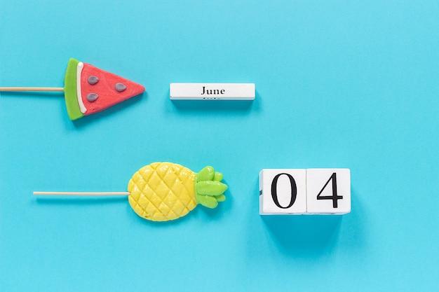 Календарная дата 4 июня и летние фрукты, конфеты, ананас, арбузные леденцы на палочке.