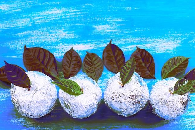 箔に包まれたシュルレアリスム4個のリンゴは天然の緑の葉です。