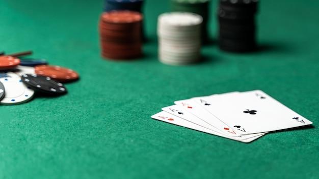 テーブル上のチップと4つのエースのスタック。ポーカーゲームのコンセプト