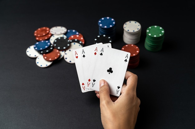 テーブルの上の4つのエースでチップと女性の手のスタック。ポーカーゲームのコンセプト