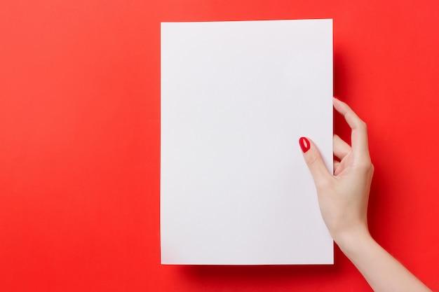Женщина руки, держа белый чистый лист а4 на красном фоне