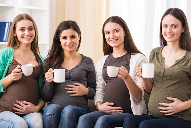 お茶を飲んで4人の幸せな妊娠中の女性。